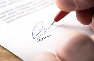 Signing contract, lease or settlement for acquisition, apartment lease, insurance, bank loan, mortgage or business buyout. Man writing name and autograph with pen. The signature is made up. Macro.