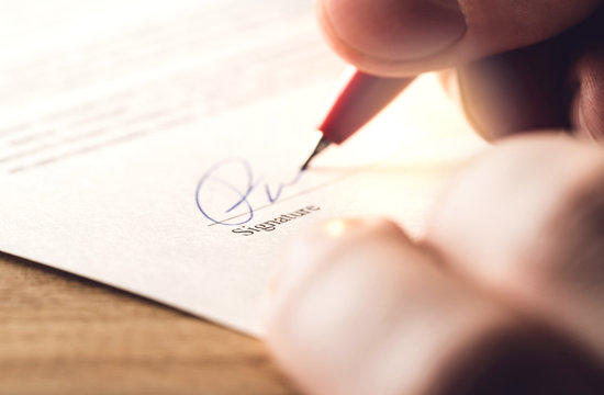 Man writing signature with pen on paper. Settlement for acquisition, business deal, bank loan or rental apartment. Signing contract, agreement, car lease or legal document. The signature is made up.