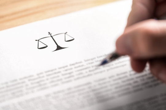 Attorney, lawyer, solicitor or jurist working on a business brief in law firm. Legal contract, clause or article paper. Man writing document with scale icon and sign with pen. Judge making decision.