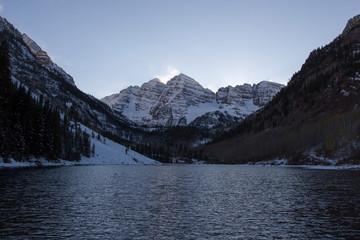 Maroon Bells at dusk in late autumn. The Maroon Bells are two peaks in the Elk Mountains in Colorado, Maroon Peak and North Maroon Peak. Both peaks are fourteeners.