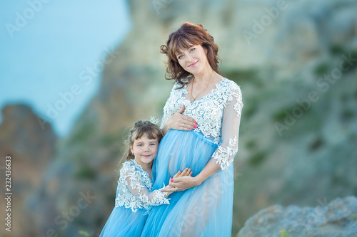 bb7778c62ee Beautiful Pregnant Woman in romantic flying dress at sea with daughter near  ancient ruins of Greece city Gorgeous pregnant girl in Greek Goddes style  ...