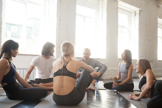 Group of fit people sitting on the floor in fitness studio room chatting, joking, laughing together. Athlete community talking in a circle on a break after practice. Teamwork, accomplishments concepts