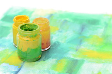 Bottles of colorful paint and paint brushs on watercolor paper,art equipments concept.