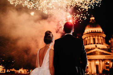 Back view of lovely married couple stand backs to camera, admire beautiful firework in night sky. Bride and groom stand closely to each other, watch salute, celebrate their wedding. Nice moment