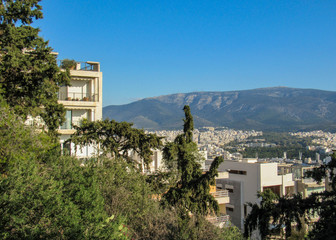 View of Athens city from Mount Hymettus with white buildings architecture, mountain, trees and blue sky