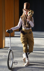 Pretty girl in a fantasy clothes with the mask and unicycle