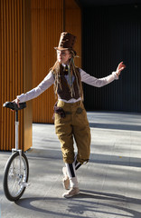Pretty girl in a fantasy clothes with unicycle