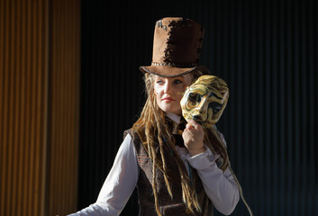 Portrait of a pretty young lady in a fantasy clothes with the mask