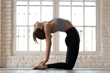 Young sporty attractive woman practicing yoga, doing Ustrasana exercise, Camel pose, working out, wearing sportswear, black pants and top, indoor full length, white yoga studio