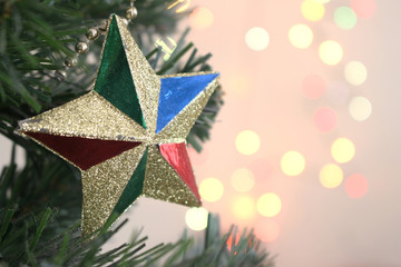 christmas tree with decorations gold star with light bokeh background