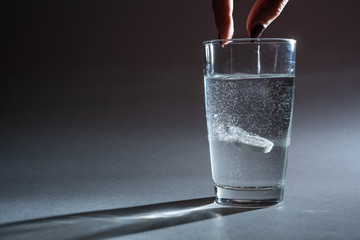 Person throwing vitamin mineral supplement effervescent tablet into glass of water. Studio shot on dark background