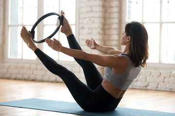 Young sporty attractive woman doing toning pilates exercise for abs and inner thighs with exercise circle, open leg balance with pilates magic circle, wearing sportswear, at yoga studio or at home