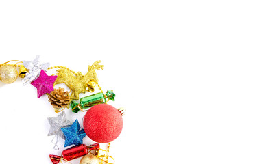 Christmas frame of decor balls, garland, beads, reindeer red pink blue golden decorations on white background. Top view.