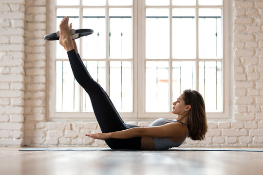 Young sporty attractive woman doing toning pilates the hundred exercise for abs with fitness circle, crunches for abdominal strength using pilates magic circle, practicing at yoga studio or at home