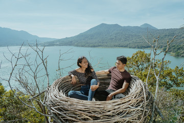 asian couple sitting on their nest on top of the hill