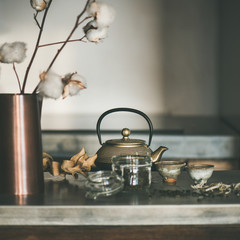 Tea ceremony. Golden iron teapot and japanese ceramic cups full of green tea drink on grey concrete kitchen counter, selective focus, square crop. Cold winter morning at home