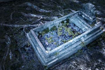 The ancient mysterious grave with cross is illuminated at night, around is the roots of trees.