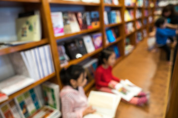 Blurred abstract background of bookshelves in book store, with children reading book in the store.
