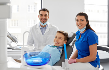 medicine, dentistry and healthcare concept - happy dentist, assistant and kid patient at dental clinic