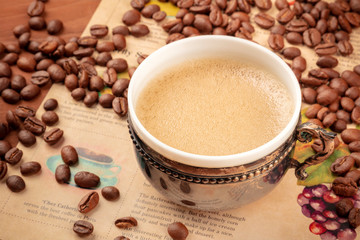 A photo of coffee in a vintage cup, with coffee beans, on an old newspaper, toned image