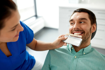 medicine, dentistry and healthcare concept - female dentist with tooth color samples choosing shade for male patient teeth at dental clinic