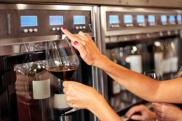 people, alcohol and lifestyle concept - close up of woman with glass pouring red wine from dispenser at bar or restaurant