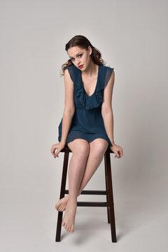 full length portrait of brunette girl wearing short blue dress.  on creamy studio background.