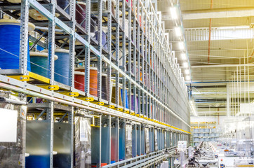 Large coils with colored electrical wires on huge shelves in an industrial plant. Manufacture of electrical wiring for cars. Employment in industry
