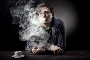 a man with glasses smokes an electronic cigarette and looks into the camera on a dark background
