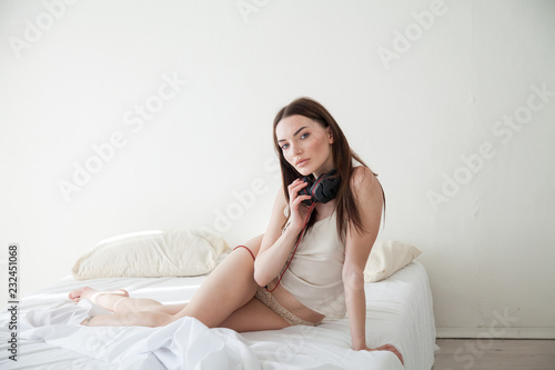 beautiful woman in pink Pajamas listening to music with headphones ... c4d50796b