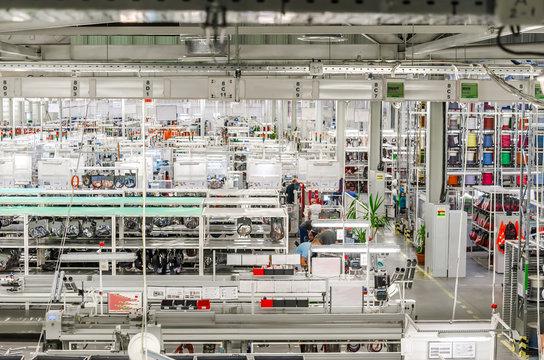 Big manufacturing enterprise. Machines, racks, fluorescent lamps. Modern business organization.
