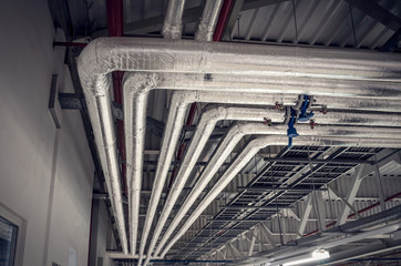 Obraz Metal pipes in thermal insulation winding on the ceiling of an industrial enterprise. - fototapety do salonu