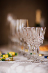 Crystal glasses with candy on the tablecloth on the table are empty