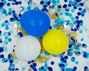 Luftballons mit blauem Konfetti, gelben Luftschlangen
