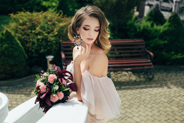The bride in a soft pink dress holds a beautiful bouquet. Wedding day