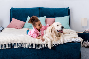 Adorable african american child lying on the bed and scratching the back of a dog