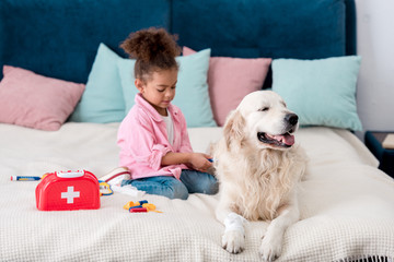 Cute african american child sitting on the bed with toys near her dog