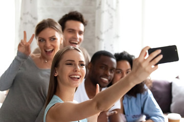 Diverse students having fun resting in cafe spends free time together, focus on female holds smartphone make selfie photo with multiracial friends smiling posing recording video for social networking