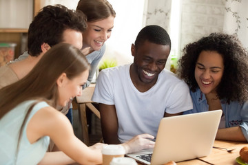 Black african guy with diverse friends watching comedy movie funny videos online using computer sitting together at desk. Friendship between multiracial people and leisure free time activities concept