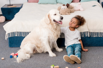 Adorable little african american child sitting on floor with happy dog
