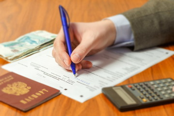 A young man calculates and completes a tax return.