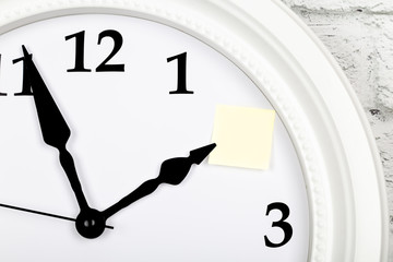 Empty sheet of paper as a reminder on the clock. Closeup view