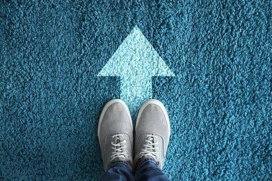 Man standing on carpet with arrow pointing in one direction. Concept of choice