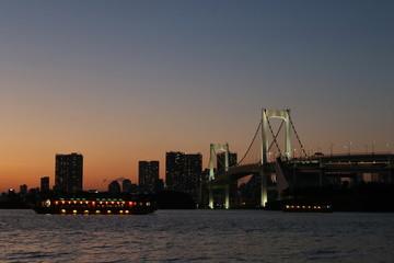 View from Odaiba Beach to Tokyo Bay with Rainbow Bridge at dusk, Tokyo, Japan