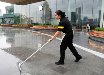 A woman cleans the wet floor near the Thailand's first flagship Apple store at Iconsiam shopping mall in Bangkok