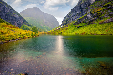 Rainy summer scene of Stavbergvatnet lake, located near Hjorundfjorden fjord, Orsta municipality, More og Romsdal county. Great morning view of Norway. Beauty of nature concept background.