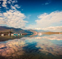 Sunny spring scene in the small fishing town - Mikrovivos. Splendid morning seascape of Aegean sea. Beauty of countryside concept background, Greece, Europe. Artistic style post processed photo.