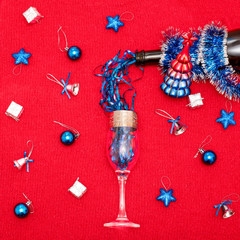 A bottle of champagne that pours blue tinsel into a glass. Background of red knitted fabric and Christmas toys.