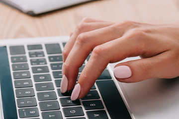 partial view of woman typing on laptop at wooden tabletop