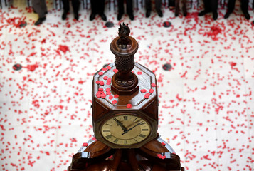 Workers stand for a poppy drop during a Remembrance Service at the Lloyd's building in the City of London